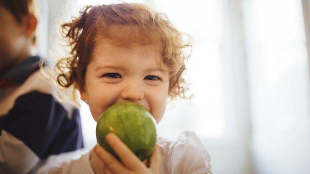 Niña comiendo una manzana.