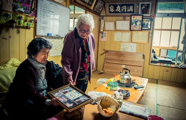 Duas mulheres de Okinawa conversam e olham fotografias