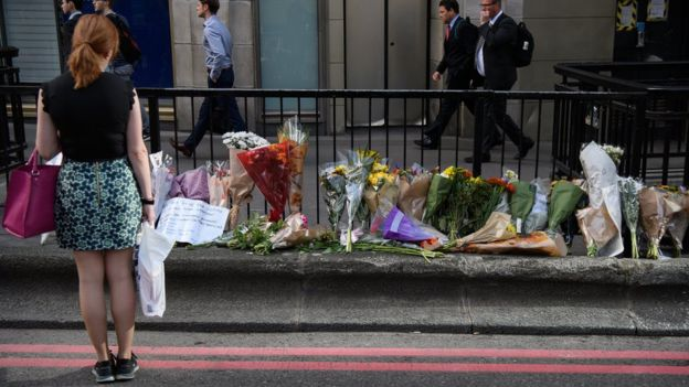 A commuter looks at some of the floral tributes on London Bridge