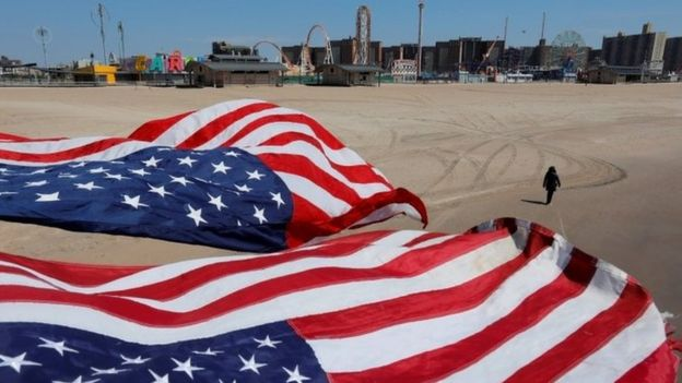 A person walks along the sand under flags of the United States of America at the Coney Island beach