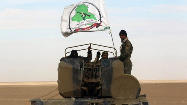 Des combattants se tiennent dans la tourelle d'un véhicule de combat d'infanterie arborant le drapeau d'une des unités des unités de mobilisation populaire alors qu'ils avancent avec les forces irakiennes dans la province d'Anbar, le 25 novembre 2017.