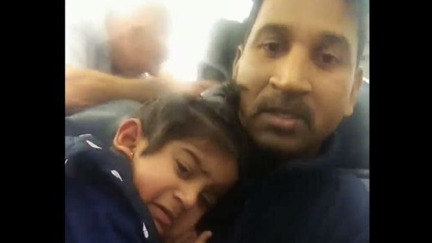 A video still of Nadesalingam holding Tharunicaa on the plane