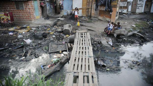 Crianças e mulher ao lado de casas precárias, além de esgoto e lixo a céu aberto