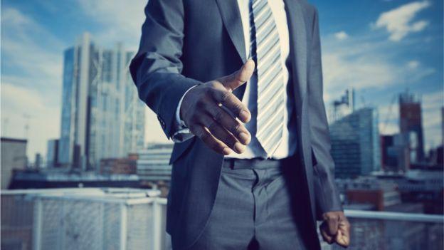 Homem negro estendendo mão para cumprimentar