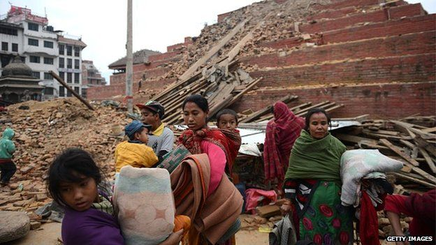 Nepalese residents walk beside buildings severely damaged by an earthquake in Kathmandu on Saturday.