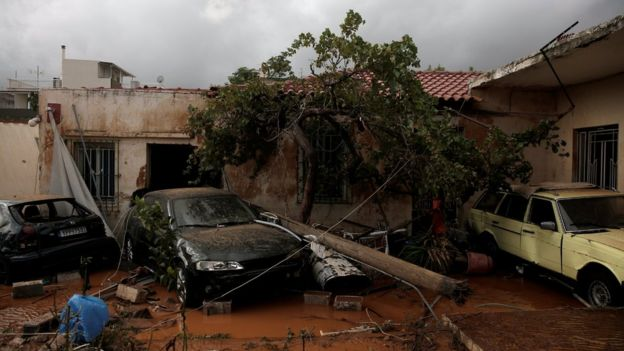 Destroyed cars are seen inside a yard following heavy rainfall in the town of Mandra