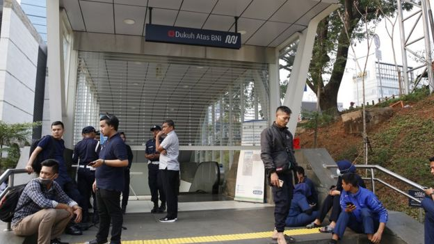 Train passengers wait by a station after a blackout in Indonesia
