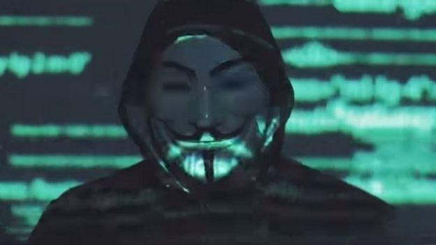 Um homem com uma máscara de Guys Fawkes em um vídeo retirado do Facebook