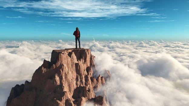 Una persona en una cumbre de una montaña mirando a las nubes debajo.