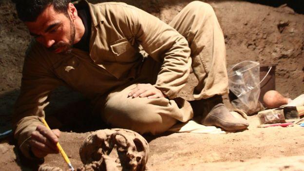 Técnico limpa esqueleto em sítio arqueológico