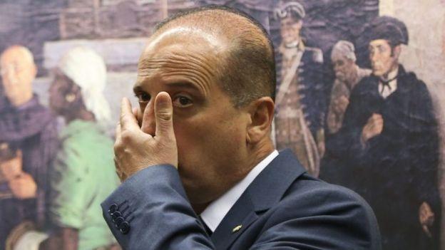 Deputado leva a mão ao rosto em frente a quadro