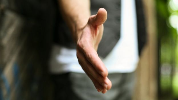 persona tendiendo la mano