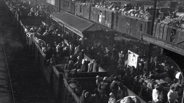 """Korean refugees are aboard a train at a station in South Korea""""s southeastern city of Daegu amid the Korean War, on 29 December 1950"""