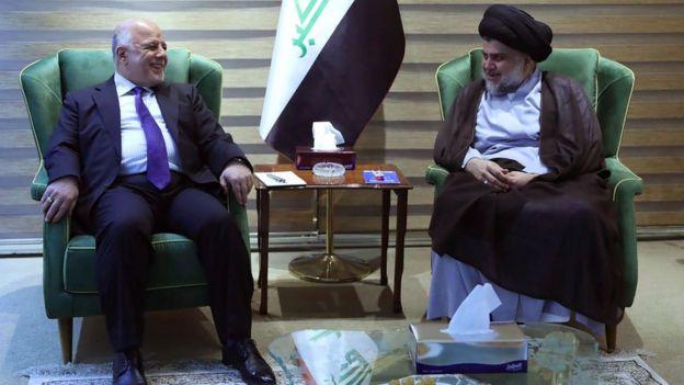 Iraqi Prime Minister Haider al-Abadi (L) talks to Moqtada Sadr (R) in Baghdad on 20 May 2018