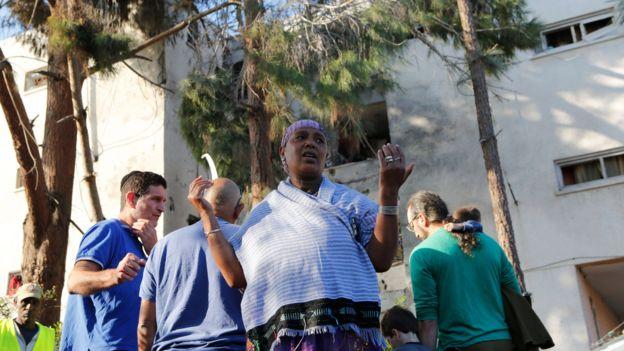 مستوطنون يتفقدون مبنى تعرض لصاروخ