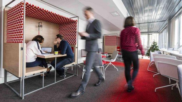 Pessoas andando em corredor e sentadas em mesa em escritório