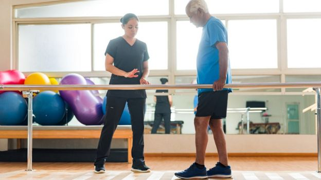 Homem faz exercício caminhando, em sala de fisioterapia, observado por profissional de saúde