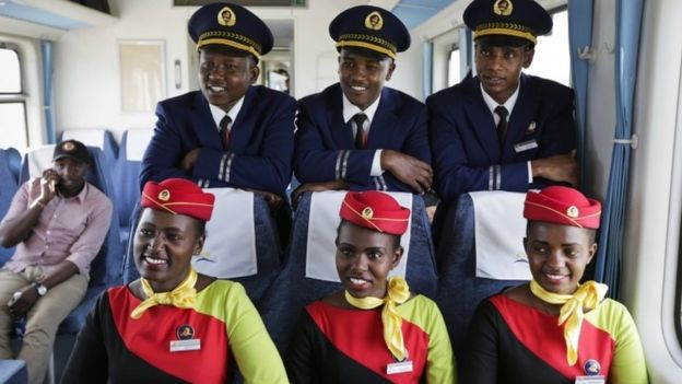Kenya Railways train attendants (R) pose for a photograph inside one of the new passenger trains using the new Mombasa to Nairobi Standard Gauge Railway (SGR), constructed by the China Road and Bridge Corporation (CRBC) and financed by Chinese government, during a test run of the train in Mombasa, Kenya, 29 May 2017