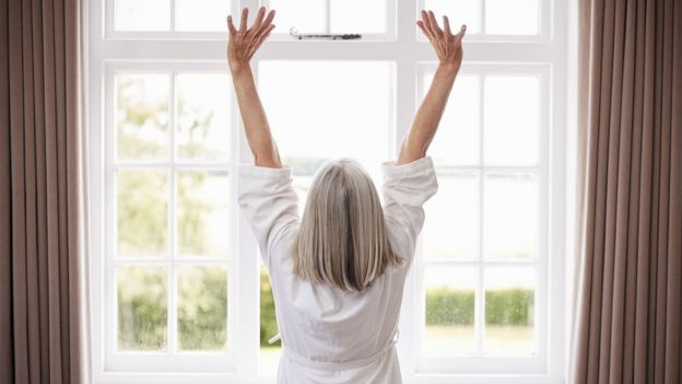 Una mujer estirándose frente a una ventana.