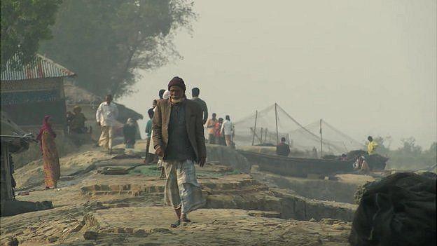 An older man walks along the shore next to a coastal town