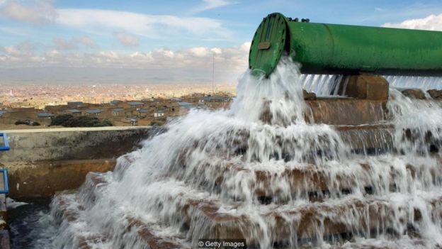Una tubería gigante deja caer agua en un pozo en una planta de tratamiento