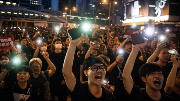 Protesters shine lights from their mobile phones during rally against a controversial extradition law proposal on 16 June 2019 in Hong Kong,