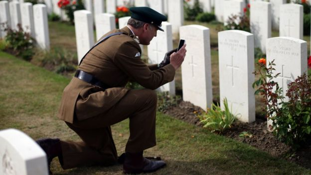 A serviceman takes a photograph in the cemetery