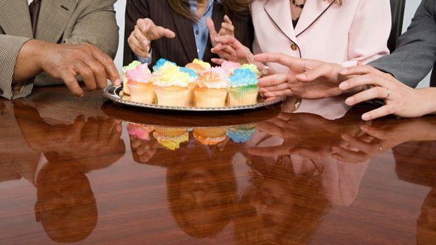 Personas rodeando una mesa con pasteles.
