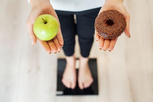 Imagem mostra mulher em pé sobre balança enquanto segura uma maçã e um donut.