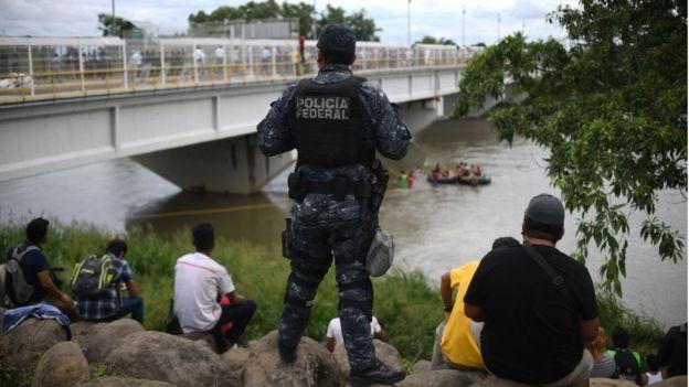 Un policía observa a migrantes en el río