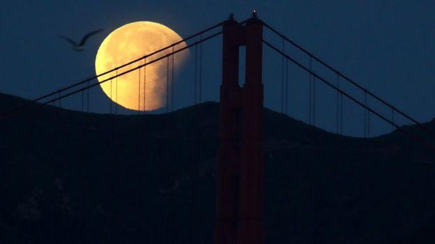 Imagen nocturna del puente Golden Gate con la luna de fondo