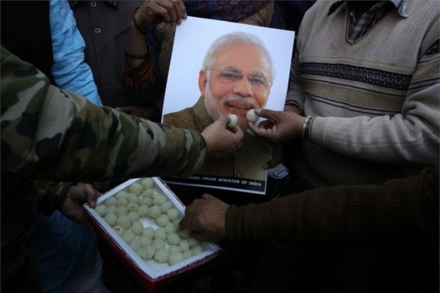 "Indian people feed sweets to a poster of Indian Prime Minister Narendra Modi as they celebrate the Indian Air Force""s air strike across the Line of Control (LoC) near the international border with Pakistan"