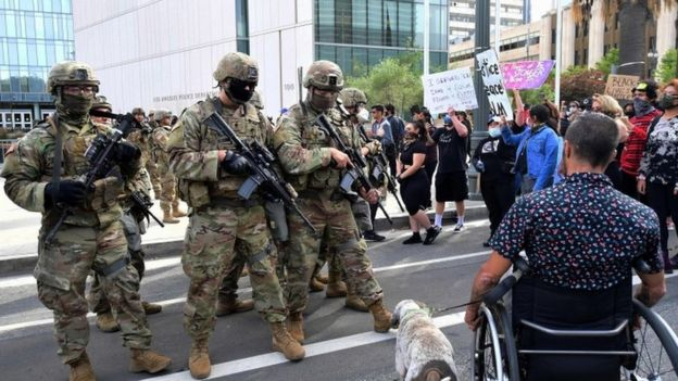 Manifestantes junto a guardias nacionales.