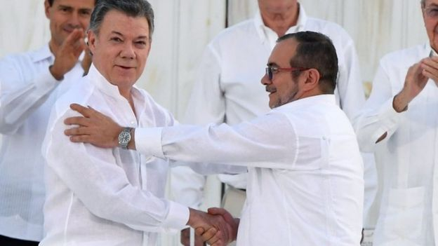President Santos and Timochenko shaking hands after signing a peace deal
