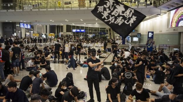 A protester waves a black flag at the Hong Kong International Airport during an anti-government protest.