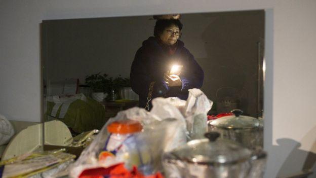 11月24日,60歲的王女士在北京周營一帶等待幫忙搬家的人。