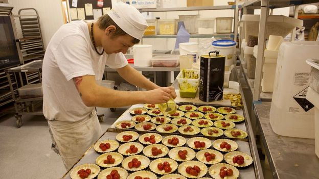 A worker makes quiches