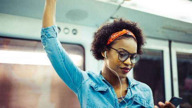 Una mujer con audífonos en el metro