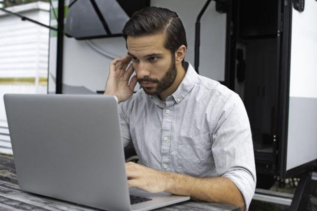 Un hombre frente a una laptop