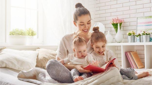 Madre leyéndole un cuento a dos niños.