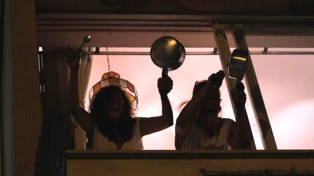 Women bang pots at the window of their apartment in Rio de Janeiro as they protest against Brazilian President Jair Bolsonaro over his handling of the coronavirus pandemic, 19 March 2020