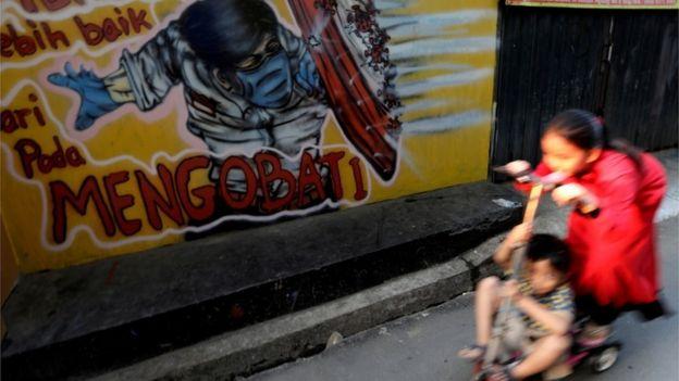Duas crianças juntas em um patinete na rua, passando ao lado de um grafite com boneco se protegendo do coronavírus