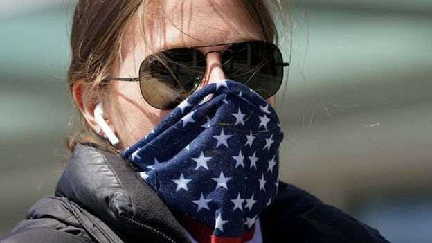 A woman wearing a stars and stripes bandana for a face mask