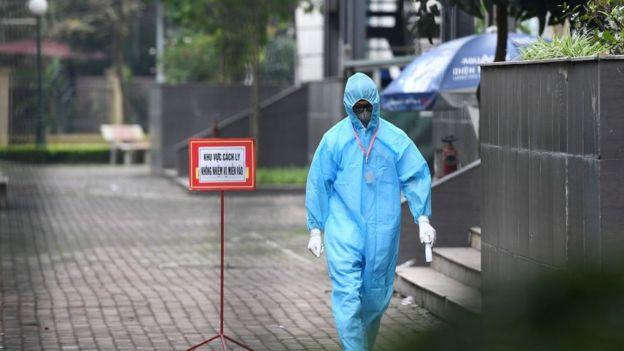 Một nhân viên y tế trước cổng một khu vực cách ly ở Thanh Trì, Hà Nội
