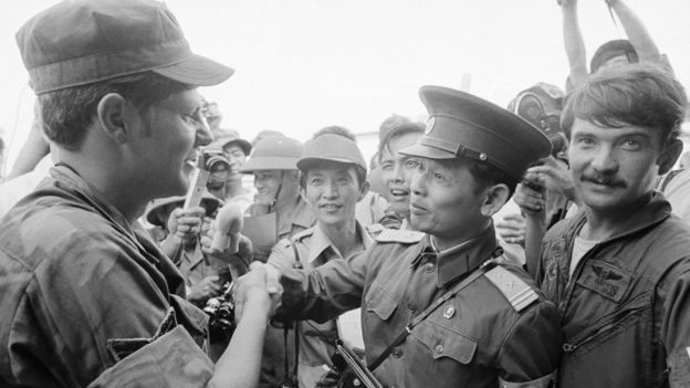 N. Vietnamese Lt. Col. Bui Tin (r), official spokesman for the N. Vietnamese delegation to the JMC, shakes hands with unidentified American Airforce SGT