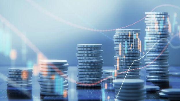 Pilhas de moedas com ilustrações de gráficos sobrepostas