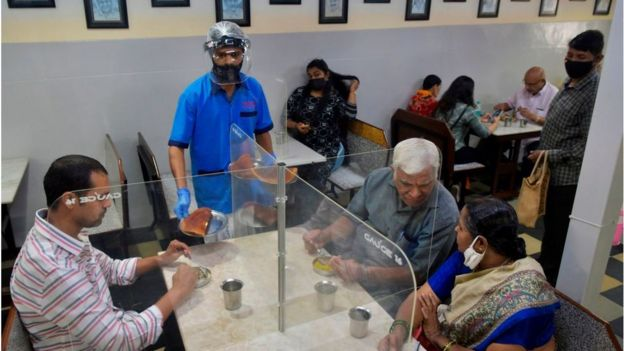 A waiter wearing a face shield and mask serves food to customers sitting in a table divided with transparent panels.