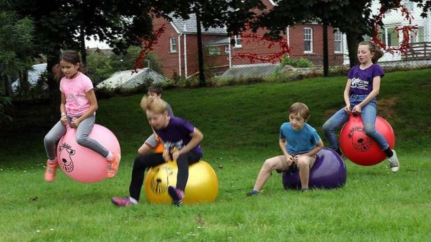 Children race on bouncy hoppers along a grassy field