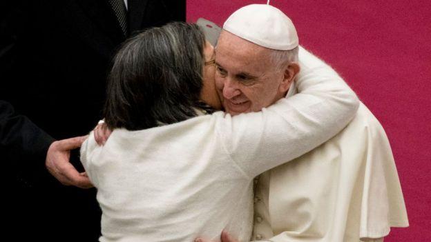 El papa Francisco abrazando a una fiel.