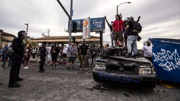 Протестующие стоят на сгоревшей полицейской машине в Лос-Анджелесе, штат Калифорния